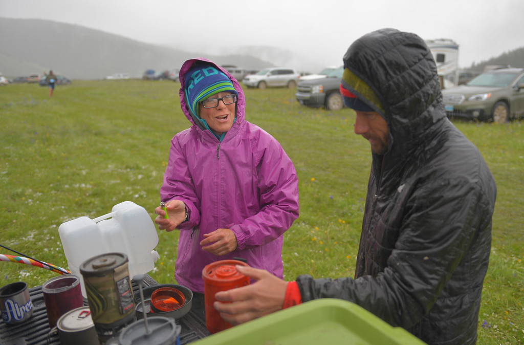 Justin Sheely | The Sheridan Press<br /> Tizz Miller, left, and Travis Vandenburgh warm up some water for their team prior to the start of the 32-mile race during the 25th annual Bighorn Mountain Wild and Scenic Trail Run Saturday at the Dry Fork aid station. Cold rain and wind brought a soggy start to Saturday's events.