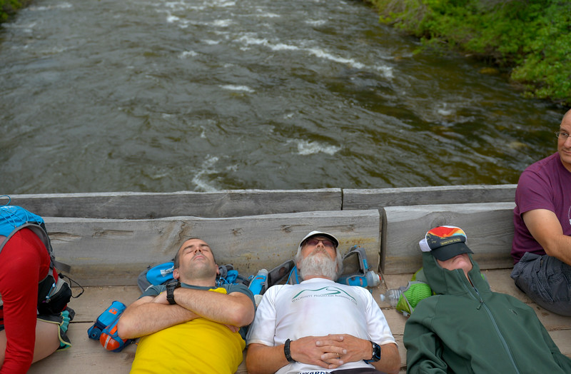 Justin Sheely   The Sheridan Press<br /> Members of the Trail Animals Running Club of Boston, Massachusetts, from left, Padraig Mullins, Bill Howard and Carolyn Shreck relax on a bridge prior to the start of the 100-mile run during the 25th Bighorn Mountain Wild and Scenic Trail Run Friday morning in the Tongue River Canyon near Dayton. Hundreds of runners from across the globe visit Sheridan and Dayton, Wyoming, to compete in the ultra marathons.
