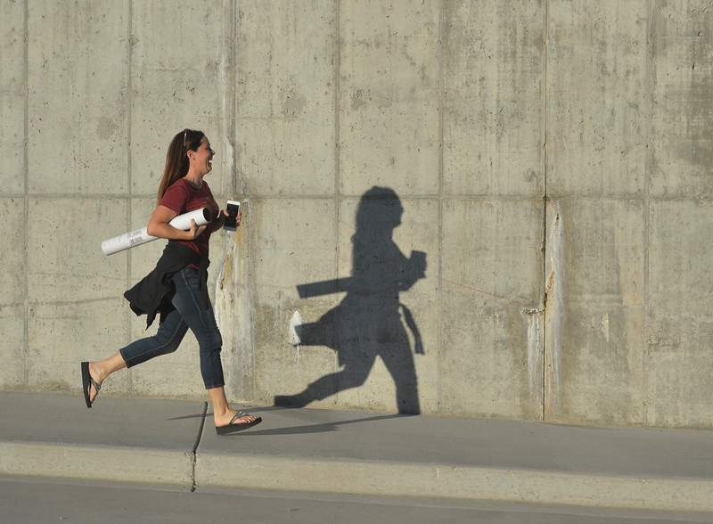 Justin Sheely | The Sheridan Press<br /> A woman runs down the sidewalk to the float staging area during Big Horn's Homecoming Parade Thursday. The Rams play Wright football under the Friday night lights in Big Horn.