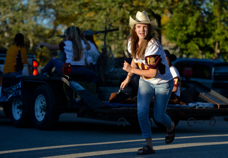 Justin Sheely | The Sheridan Press<br /> Sophomore student Courtney Wallach leaves her float to give candy to children during Big Horn's Homecoming Parade Thursday. The Rams play Wright football under the Friday night lights in Big Horn.
