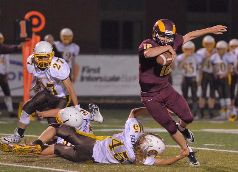 Justin Sheely | The Sheridan Press<br /> Big Horn's quarterback Quinn McCafferty keeps the ball for a run as Grizzlies' Wyatt Horrocks make a tackle during the Rams first home game Friday night at Big Horn High School. The Rams won 44-14 over Rocky Mountain class 1a football.