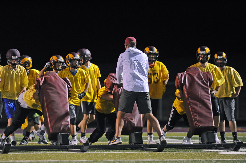 The Big Horn football team pushes assistant coach Andrew Marcure on the sled during midnight practice on Wednesday, Aug. 9 at Big Horn High School. Mike Pruden | The Sheridan Press