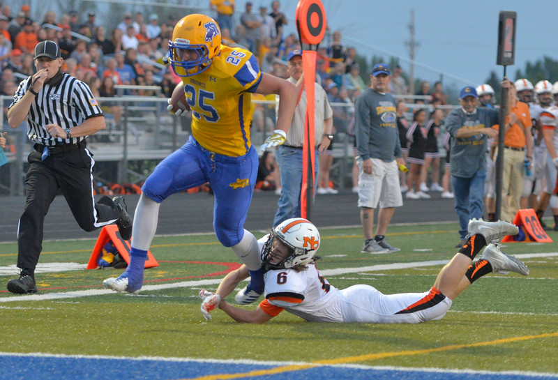 Justin Sheely | The Sheridan Press<br /> Sheridan's Parker Christensen runs into the end zone as Natrona's Seth Cisneros tumbles during the game Friday night at Sheridan High School. The Broncs held on to win 37-34 in overtime.