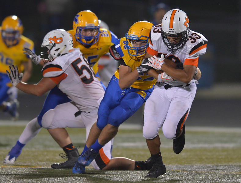 Justin Sheely | The Sheridan Press<br /> Sheridan defensive lineman Quinton Brooks hits Natrona County's Dante Wallace during the game against the Mustangs Friday night at Sheridan High School. The Broncs held on to win 37-34 in overtime.
