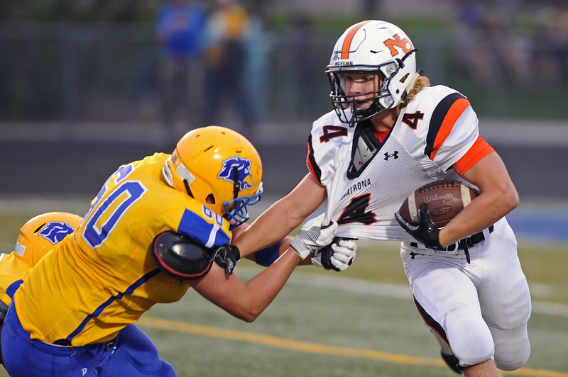 Connor Jorgenson, left, latches on to the jersey of Natrona running back Brett Brenton on Friday, Sept. 8 at Homer Scott Field. Mike Pruden | The Sheridan Press