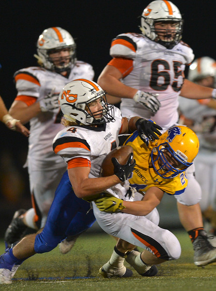 Natrona's Brett Brenton is stopped by Sheridan's Kyle Custis during the game against the Broncs Friday night at Sheridan High School. Sheridan won in overtime 37-34. Justin Sheely | The Sheridan Press