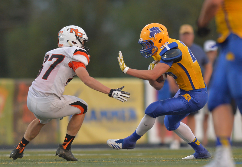 Justin Sheely | The Sheridan Press<br /> Sheridan's Parker Christensen runs against Natrona's Riley Shepperson during the game Friday night at Sheridan High School. The Broncs held on to win 37-34 in overtime.