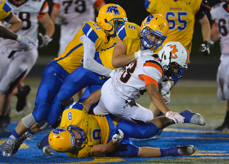 Justin Sheely | The Sheridan Press<br /> Sherdan's Bryce Taylor (21) and Garret Coon (5) stop Natrona's Dante Wallace on top of Samuel Boyles (8) during the game against the Mustangs Friday night at Sheridan High School. The Broncs held on to win 37-34 in overtime.