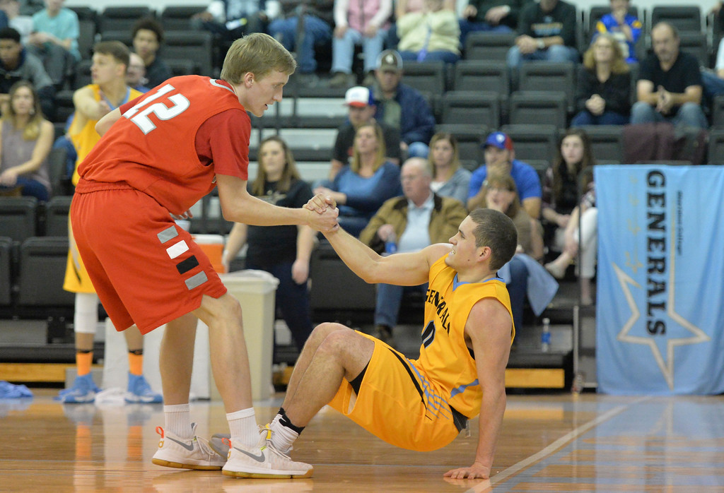 Justin Sheely | The Sheridan Press<br /> Trappers player Marshall McArthur helps Sheridan's Celio Araujo up from the floor during the first round of the Region 9 north tournament Saturday at the Bruce Hoffman Golden Dome. Sheridan won 62-58 over the Northwest Trappers.