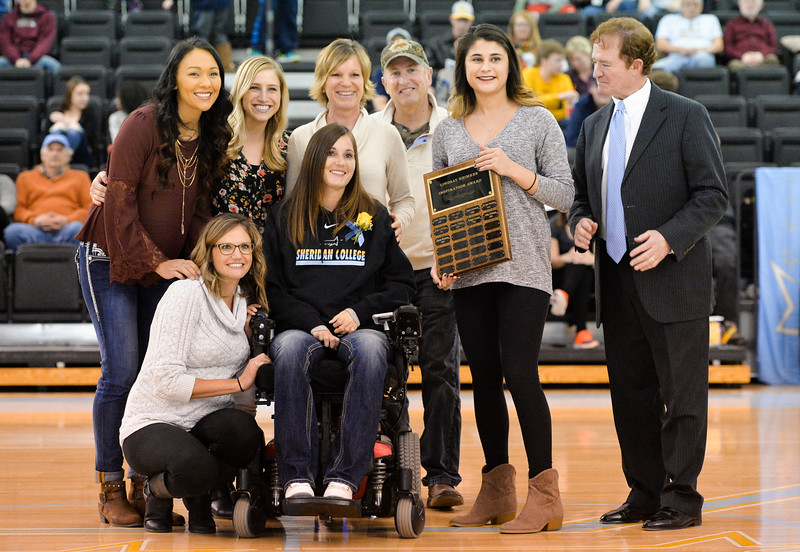 Justin Sheely | The Sheridan Press<br /> Former Sheridan College Women's Basketball player Lindsay Heimkes, center, presents her Inspiration Award to Lady General Quriss Romero, right, as women's head coach Fram McCarthy looks on during halftime of the men's game last Saturday in the Bruce Hoffman Golden Dome. Heimkes played for the Lady Generals but was severely injured in a car accident in 2006.