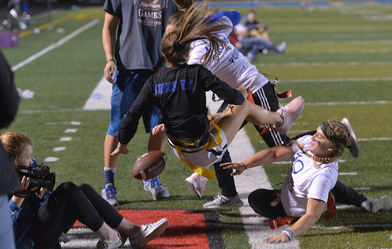 Justin Sheely | The Sheridan Press<br /> Senior Gracie Von Krosigk falls into the sideline as she is tackled by junior's Braylee Standish, right, at powderpuff football during Sheridan's homecoming week Wednesday at Scott Field. The junior class beat the seniors in the winners' game 18-12. The pep rally is Thursday night on Grinnell Plaza.