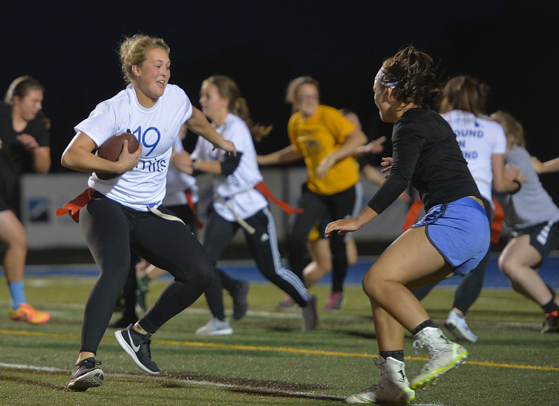 Justin Sheely | The Sheridan Press<br /> Junior Jordan Christensen rushes against the freshmen at powderpuff football during Sheridan's homecoming week Wednesday at Scott Field. The junior class beat the seniors in the winners' game 18-12. The pep rally is Thursday night on Grinnell Plaza.
