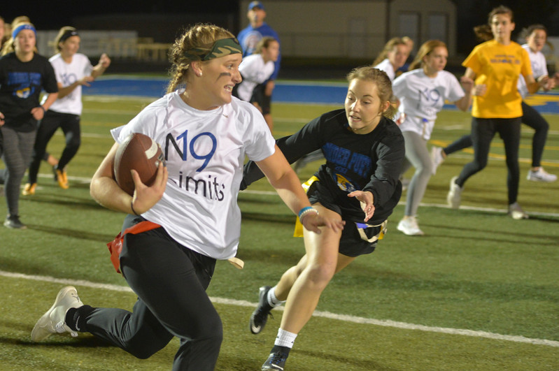 Justin Sheely | The Sheridan Press<br /> Juniors' Braylee Standish runs the ball against seniors' Alli Puuri at powderpuff football during Sheridan's homecoming week Wednesday at Scott Field. The junior class beat the seniors in the winners' game 18-12. The pep rally is Thursday night on Grinnell Plaza.