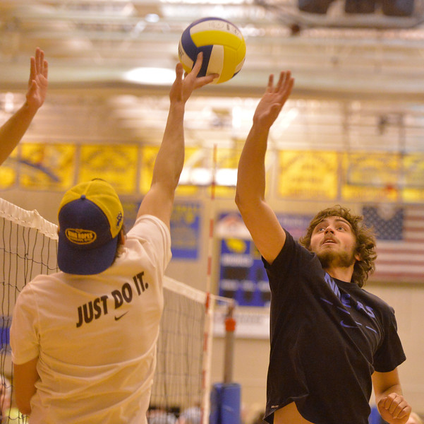 Justin Sheely | The Sheridan Press<br /> Sheridan seniors Aaron Sessions, left, and Aaron Woodward hit the ball against the juniors in He-Man Volleyball on Homecoming week Tuesday at Sheridan High School.