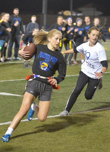 Justin Sheely | The Sheridan Press<br /> Senior Kayleee Abernathy runs the ball against the juniors at powderpuff football during Sheridan's homecoming week Wednesday at Scott Field. The junior class beat the seniors in the winners' game 18-12. The pep rally is Thursday night on Grinnell Plaza.
