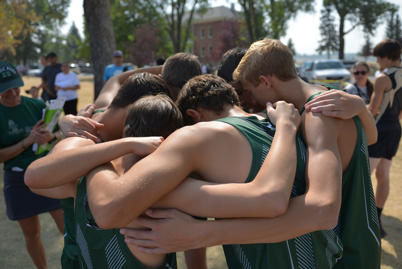 Justin Sheely | The Sheridan Press<br /> Tongue River High School boys pause to pray before competing in the Michelle Ludwig Cross-County invite Saturday at the Sheridan Veterans Affairs Campus.