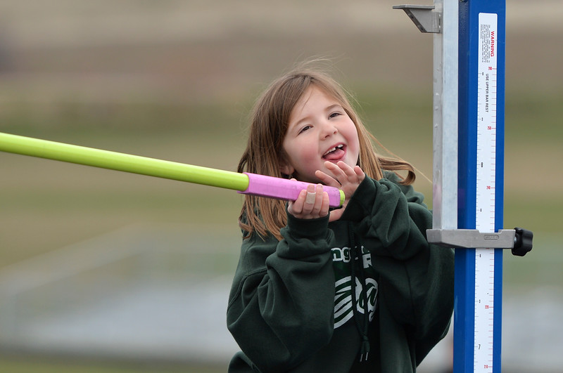 Justin Sheely | The Sheridan Press<br /> Volunteer Caelin Reish, 7, replaces the bar for the high jump during the pre-prom track and field invite Friday at Tongue River High School in Dayton.