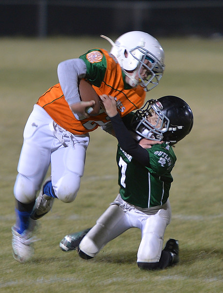 Justin Sheely | The Sheridan Press<br /> Canes' Kolin Custis gets tackled by Tongue River's Connor Cummins Tuesday night for the Sheridan Recreation District 5th and 6th grade Little Guy Football Championship at Dan Madia Field. The Outlaws were tied 0-0 in a defensive battle against the Canes into the fourth quarter. Momentum turned when Tongue River caught an interception late in the fourth quarter and the Outlaws offence rallied to win 8-0 in overtime.