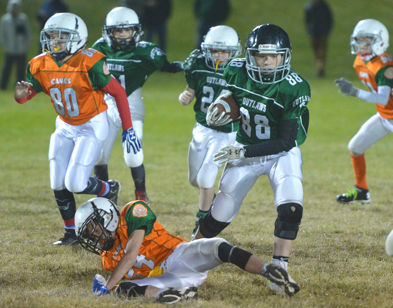 Justin Sheely | The Sheridan Press<br /> Tongue River's Colter Hanft escapes Canes' Dane Steel Tuesday for the Sheridan Recreation District 5th and 6th grade Little Guy Football Championship at Dan Madia Field. The Outlaws were tied 0-0 in a defensive battle against the Canes into the fourth quarter. Momentum turned when Tongue River caught an interception late in the fourth quarter and the Outlaws offence rallied to win 8-0 in overtime.