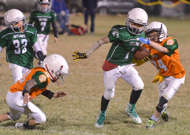 Justin Sheely | The Sheridan Press<br /> Tongue River's Caleb Kilbride runs the ball against Canes' Dane Steel, right, Tuesday night at the Sheridan Recreation District 5th and 6th grade Little Guy Football Championship at Dan Madia Field. The Outlaws were tied 0-0 in a defensive battle against the Canes into the fourth quarter. Momentum turned when Tongue River caught an interception late in the fourth quarter and the Outlaws offence rallied to win 8-0 in overtime.
