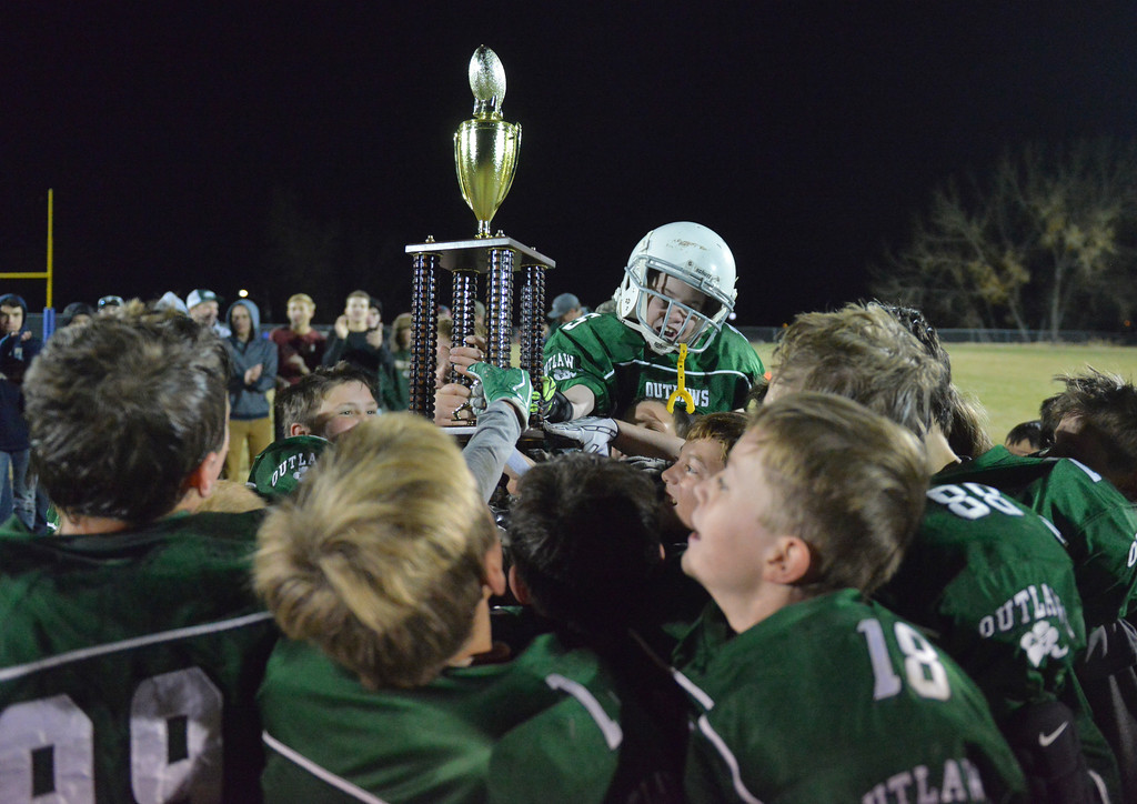 Justin Sheely | The Sheridan Press<br /> The Tongue River Outlaws celebrate Tuesday night at the Sheridan Recreation District 5th and 6th grade Little Guy Football Championship at Dan Madia Field. The Outlaws were tied 0-0 in a defensive battle against the Canes into the fourth quarter. Momentum turned when Tongue River caught an interception late in the fourth quarter and the Outlaws offence rallied to win 8-0 in overtime.