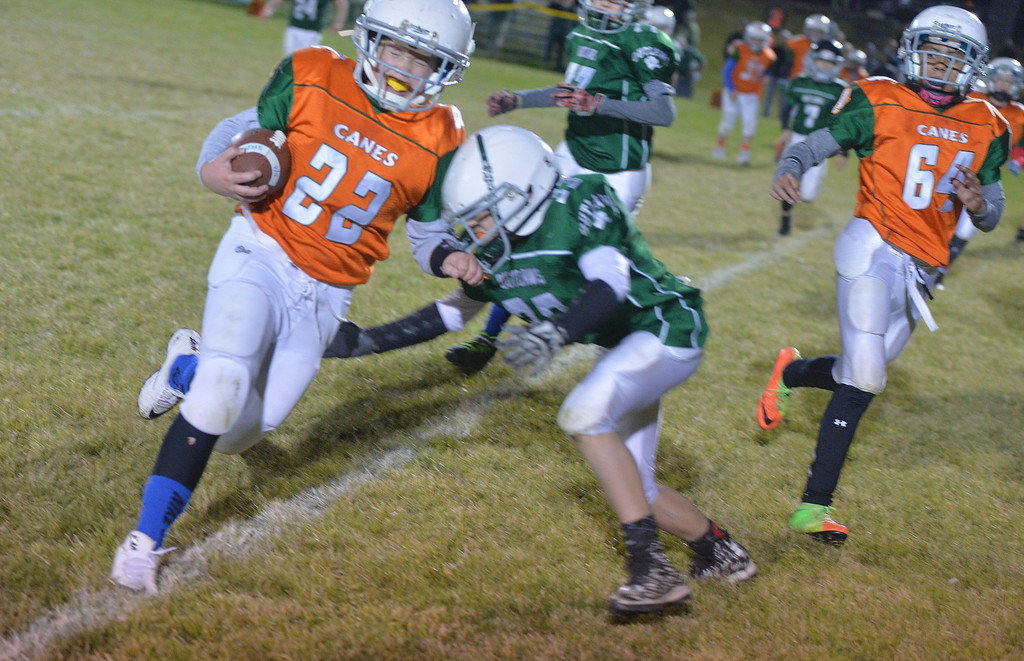 Justin Sheely | The Sheridan Press<br /> Canes' Kolin Custis is tackled by Tongue River's Alex Barker in an overtime possession Tuesday night at the Sheridan Recreation District 5th and 6th grade Little Guy Football Championship at Dan Madia Field. The Outlaws were tied 0-0 in a defensive battle against the Canes into the fourth quarter. Momentum turned when Tongue River caught an interception late in the fourth quarter and the Outlaws offence rallied to win 8-0 in overtime.