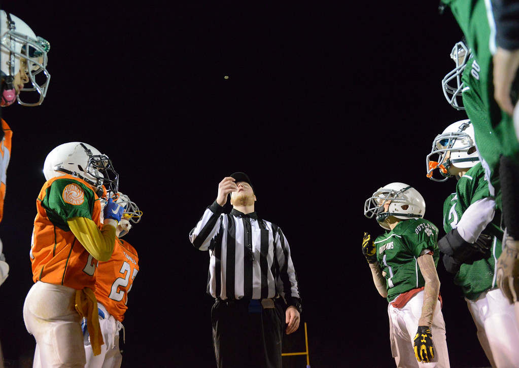 Justin Sheely | The Sheridan Press<br /> Game official flips a coin as the Canes, left, battle the Tongue River Outlaws Tuesday for the Sheridan Recreation District 5th and 6th grade Little Guy Football Championship at Dan Madia Field. The Outlaws were tied 0-0 in a defensive battle against the Canes into the fourth quarter. Momentum turned when Tongue River caught an interception late in the fourth quarter and the Outlaws offence rallied to win 8-0 in overtime.