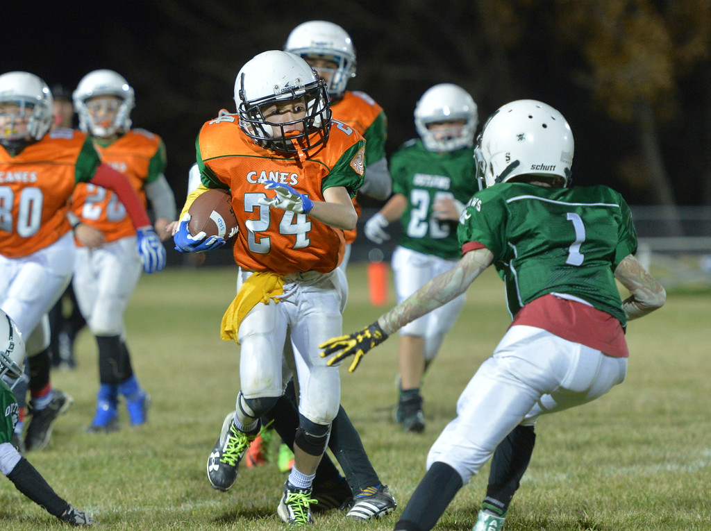 Justin Sheely | The Sheridan Press<br /> Canes' Kailen Elliot runs the ball against the Tongue River Outlaws Tuesday for the Sheridan Recreation District 5th and 6th grade Little Guy Football Championship at Dan Madia Field. The Outlaws were tied 0-0 in a defensive battle against the Canes into the fourth quarter. Momentum turned when Tongue River caught an interception late in the fourth quarter and the Outlaws offence rallied to win 8-0 in overtime.