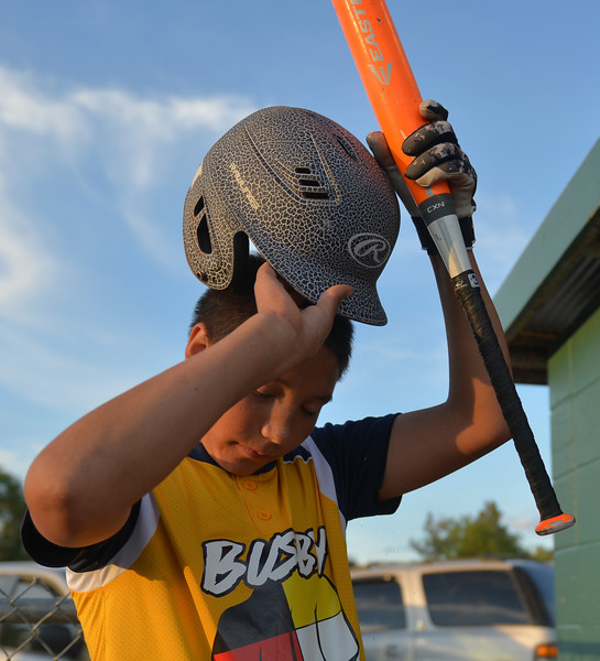 Justin Sheely | The Sheridan Press <br /> Busby's Lighting Kellum puts his batting hat on during the last regular season Webb Wright League game Thursday at the 6th Street Fields in Sheridan. The team from Busby, Montana, beat Sheridan's Dodgers 3-1. The playoffs begin next week.
