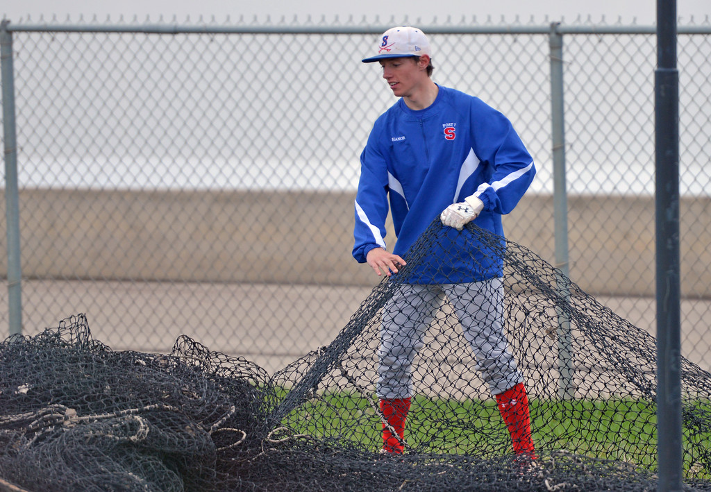 Jeffrey Shanor untangles a net to be hung up on the batting cages at Thorne-Rider Stadium on Monday, April 3. Monday was the first practice of the season for the Sheridan Jets and Troopers baseball teams. Mike Pruden | The Sheridan Press