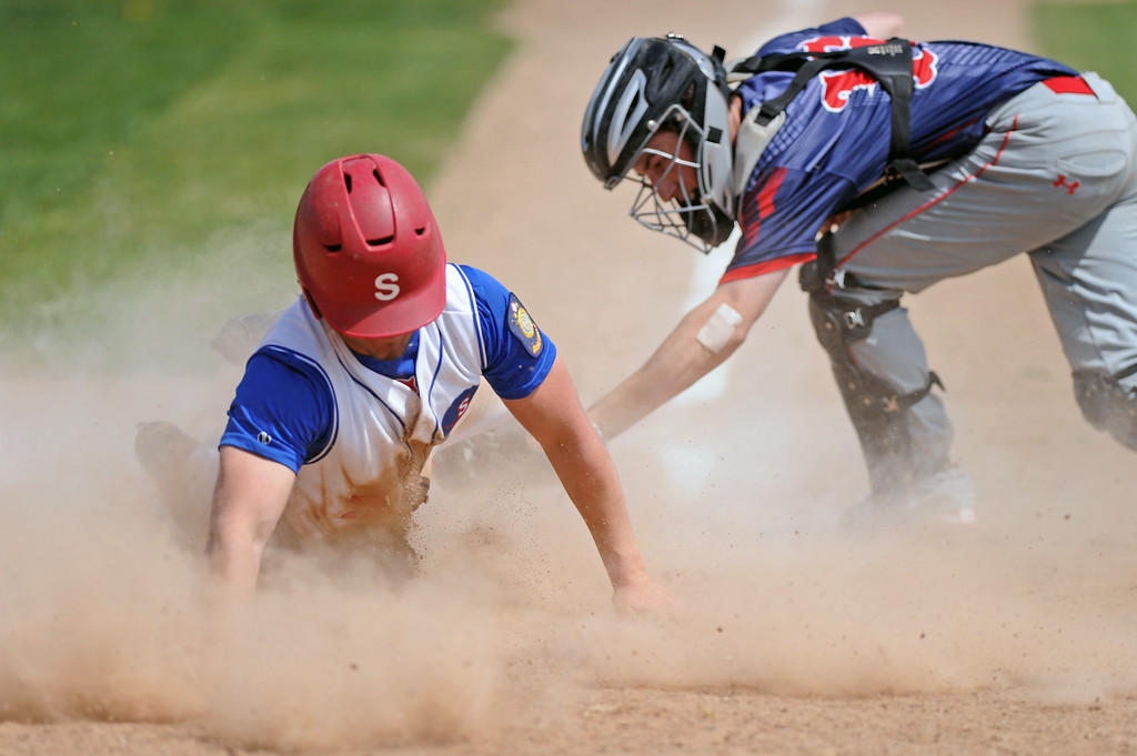 Blake King, left, loses his helmet as he avoids a tag at home plate on Sunday, May 7 at Thorne-Rider Stadium. Mike Pruden | The Sheridan Press
