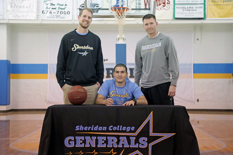 Sheridan College assistant men's basketball coach Tom Parks, left, and head coach Matt Hammer, right, join Celio Araujo as he signs a letter of intent to play for the University of Maine next fall. Mike Pruden | The Sheridan Press