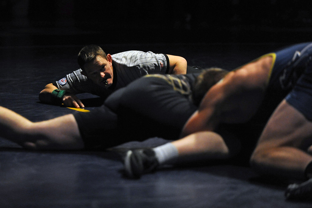 Referee Lanny Schneider gets low to the mat as he scores a match between Sheridan and Billings West on Tuesday, Jan. 3 at Sheridan High School. Mike Pruden   The Sheridan Press