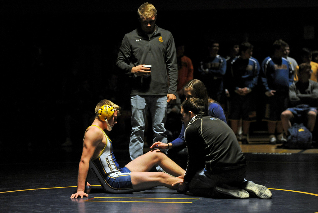Head coach Tyson Shatto and trainer Joanne Brewster work to relieve wrestler Chance Quarterman's calf cramp during the 145-pound match against Billings West on Tuesday, Jan. 3 at Sheridan High School. Mike Pruden   The Sheridan Press