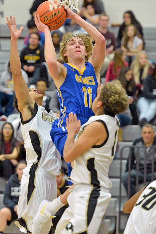 Drew Boedecker squeezes between two defenders on his way to the rim on Friday, March 20 at South High School. Mike Pruden | The Sheridan Press