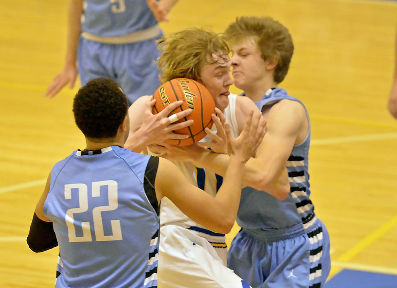 Drew Boedecker gets mugged by two Cheyenne East defenders as he drives down the lane on Saturday, Jan. 28 at Sheridan High School. Mike Pruden | The Sheridan Press