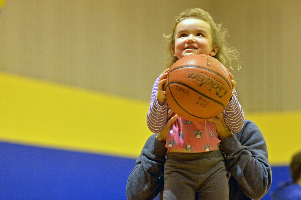 Hannah Mowry gets a little help from her mom as she shoots a basketball during the halftime pop shot contest on Friday, Jan. 13 at Sheridan High School. Mike Pruden | The Sheridan Press