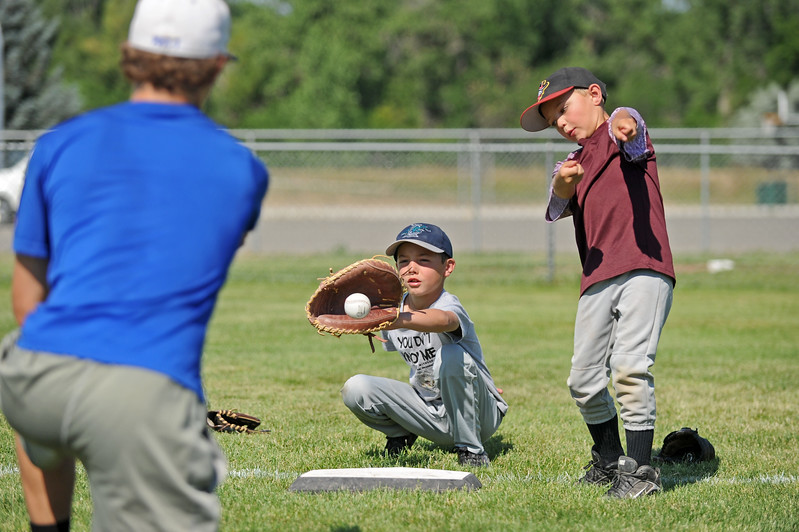Ridge Franklin, right, takes a mock swing as Riley Friday works on his catching skills at Troopers baseball camp on Friday, July 7 at Thorne-Rider Stadium. Mike Pruden | The Sheridan Press