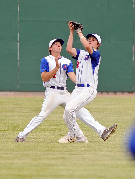 Coy Steel, left, avoids a collision as Andrew Ratty snatches a fly ball during Sheridan's 8-7 win over Laurel on Wednesday, July 5 at Thorne-Rider Stadium. Mike Pruden | The Sheridan Press