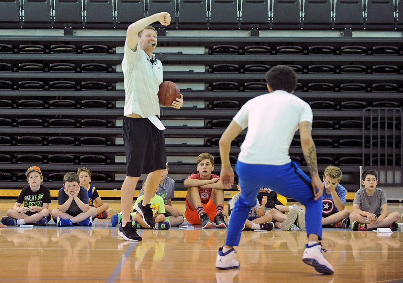 Head coach Matt Hammer implies a charge while demonstrating a defensive drill during Sheridan College men's basketball camp on Wednesday, June 14 at the Bruce Hoffman Golden Dome. Mike Pruden | The Sheridan Press