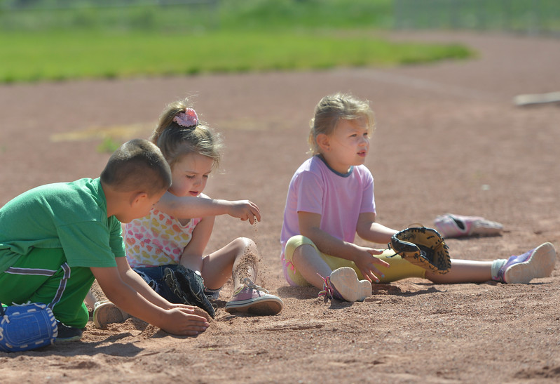 Justin Sheely | The Sheridan Press<br /> From left, Max Alley, Raegan Rosselott and Abby Cutright are distracted from practice by playing with dirt during Itty Bitty T-Ball basics Wednesday at the Ranchester Ball Field. Tongue River Valley Community Center offered a four day introduction aimed at youngsters, between ages four and five, to learn the basics of t-ball.