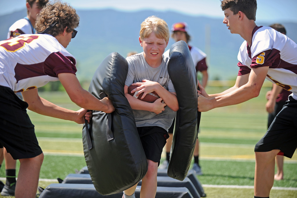 Cole Riesen fights through two Big Horn High School tacklers during the Justin O'Dell Memorial Football Camp on Thursday, June 8 at Big Horn High School. Mike Pruden | The Sheridan Press