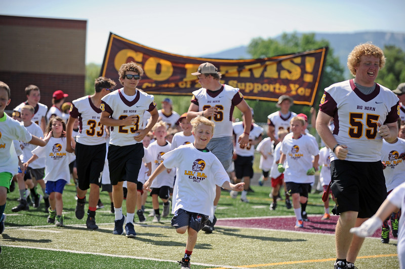 Members of the Big Horn High School football team run onto the field with participants at the Lil' Ram Football Camp on Thursday, June 8 at Big Horn High School. Mike Pruden | The Sheridan Press