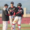 East Rock's coach meets with his pitcher and catcher on the mound after a couple of Page scores.
