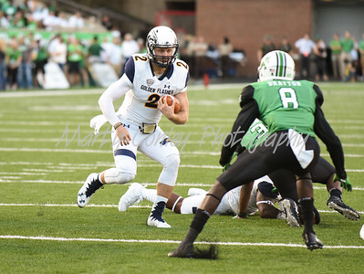 Kent State quarterback, George Bollas looks for running room as Marshall's Brandon Drayton applies pressure on Saturday evening.  MARTY CONLEY/ FOR THE DAILY INDEPENDENT
