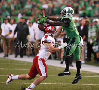 Marshall's Trey Rodriquez reaches for the ball as Miami's Brad Koenig pressures on Saturday evening.  MARTY CONLEY/ FOR THE DAILY INDEPENDENT