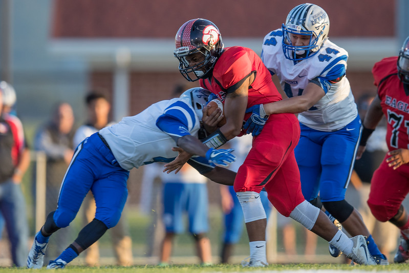 Jwan Evans powers his way to a few extra yards against Lee's Ta'Corrios Strother (4) and Ethan Vest (44)