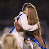 Homecoming Queen and King meet at center field for a hug after being announced
