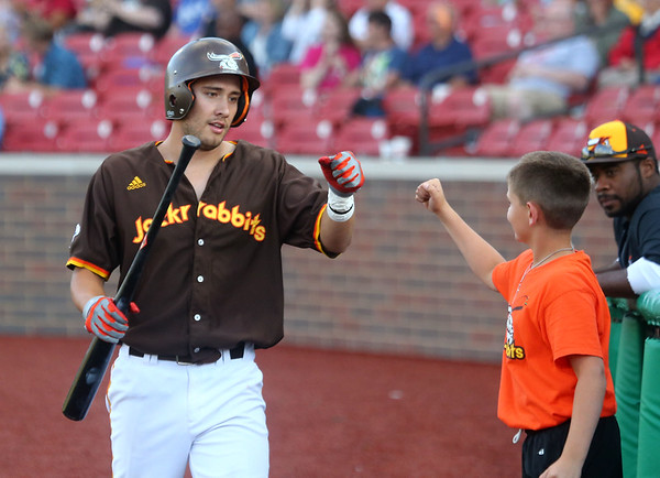 6-6-17<br /> Jackrabbits vs Aviators<br /> Alex Del Rio fist bumps one of the bat boys in the dugout after scoring the Jackrabbits' only run.<br /> Kelly Lafferty Gerber | Kokomo Tribune
