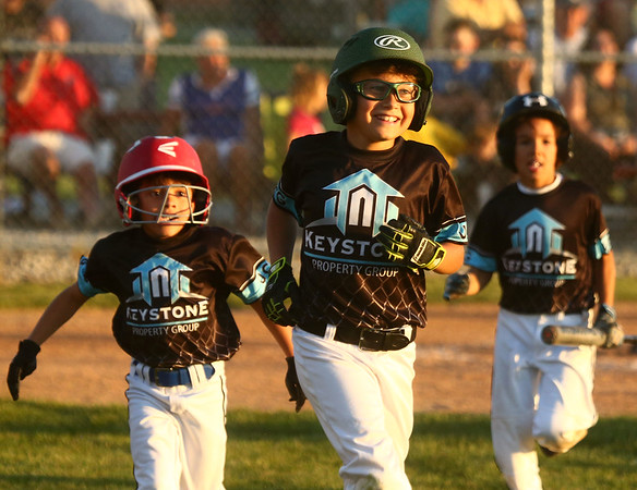 6-28-17<br /> Keystone vs Top of the Line Howard County Rookie tournament championship<br /> Hagen Smith, center, of Keystone, grins after stepping off home base. With his hit, Keystone was able to score three runs.<br /> Kelly Lafferty Gerber | Kokomo Tribune